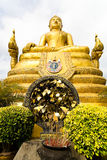 Sculpture of a golden Buddha and leaves of a tree with desires. Royalty Free Stock Photos