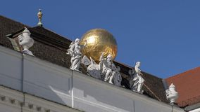 Sculpture with golden globe atop the State Hall of the Austrian National Library, seen from Josefsplatz. A public square located at the Hofburg Palace in stock image