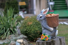 Sculpture of a hare carrying a basket with fir cones Stock Images
