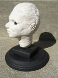 Sculpture of a head in clay. White clay sculpture of a head on a black stand royalty free stock image