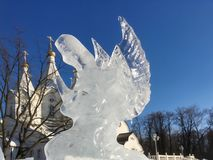 Sculpture of the icy angel on the background of a white temple. Royalty Free Stock Photo