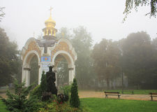 The Sculpture Of Jesus Christ. The sculpture of the praying of Jesus Christ in a thorny wreath on the background of the gazebo with a cross. The foggy weather Royalty Free Stock Photos