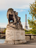 Sculpture lion on bridge of Alexandre III with Eiffel Tower on the background. Stock Images