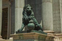 Sculpture lion cast in bronze on building facade in Madrid. Sculpture of imposing lion cast in bronze on the front facade of Palacio de las Cortes, in a sunny stock images