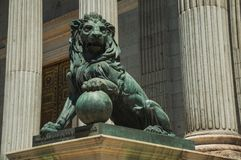Sculpture lion cast in bronze on building facade in Madrid. Sculpture of imposing lion cast in bronze on the front facade of Palacio de las Cortes, in a sunny royalty free stock photography