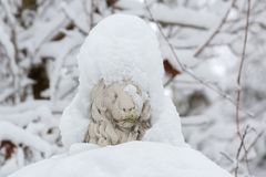 Sculpture of a lion covered with snow. Park sculpture of a lion covered with snow. Close-up view Royalty Free Stock Image