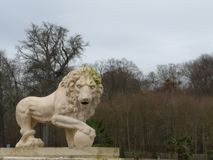Sculpture of a lion of Medici with a ball in the paw in the park National Domain of Saint Cloud. Sculpture of a lion of Medici with a ball in the paw in the royalty free stock photo