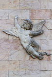 Sculpture of Little Angel Boy. Sculpture of angel boy with wings hanging on the strong wall Royalty Free Stock Photos