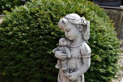 Sculpture of a little girl. Little girl holding a teddybear Royalty Free Stock Images