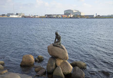 The sculpture of the little Mermaid on the background of the Harbor waterfront. Copenhagen, Denmark Royalty Free Stock Photo