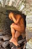 Sculpture made of wood of a naked man under a stone arch. Wooden sculpture of a crouching naked man under a stone arch. Traditional wood carving art in the Stock Images