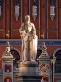 Sculpture of man with sword. Sculpture of Roland holding sword and House of the Blackheads behind it Royalty Free Stock Photo