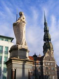 Sculpture of man with sword and church behind it. Sculpture of Roland and St. Peter's Cathedral (Town Hall square, Riga, Latvia Stock Images