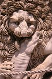 Sculpture of a medieval lion head of stone who keeps prey in his paws Italy. Sculpture of a medieval lion head of stone Italy Royalty Free Stock Image