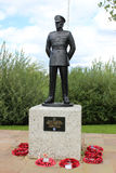 Military Police, National Memorial Arboretum. The sculpture of a military policeman in uniform standing on a plinth with poppy wreaths around the base is a Royalty Free Stock Photography