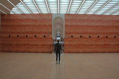 Sculpture modern architecture. Sculpture of a human figure in a modern architecture room with glass ceiling and marble tile floor and walls Royalty Free Stock Image
