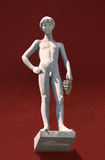 Sculpture of a naked boy with grapes. Standing on a socket in front of a red house wall Royalty Free Stock Images