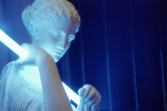 Sculpture with neon light. Greek sculpture holding blue neon light. aphrodite godess of love. outside nightclub Royalty Free Stock Photo