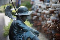 Sculpture Of Little Boy Fishing In The Garden. Stock Photos