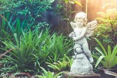 Sculpture ou statue blanche en cupidon se tenant dans le jardin extérieur entouré avec naturel vert Image stock