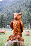 Sculpture of an owl on a tree trunk. In a park in the dolomites in Italy Royalty Free Stock Photos