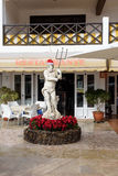 Sculpture of Poseidon decorated with Santa's hat at yard of restaurant Stock Photos