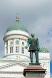 Sculpture of the Russian Emperor Alexander II (1894) on  background of the dome of St. Nicholas Cathedral on a cloudy da Royalty Free Stock Photo