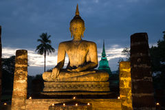 Sculpture of the sitting Buddha in night illumination against the background of the gloomy sky. Sukhothai, Thailandd Royalty Free Stock Photography