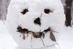 Creepy snowman face. Sculpture of snow. Strange and terrifying snowman. Playing outdoors in winter. Family winter fun in the forest. Smile and nose of a snowman stock photography