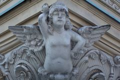 Sculpture of a staring angel. A sculpture of a staring angel under the roof of a balcony Stock Image