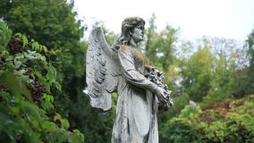 Sculpture of stone angel praying at the cemetery Stock Photos
