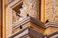 Sculpture surrounded by pigeons o the beautiful facade of La Merced Church in Antigua stock photography