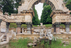 Sculpture under the ancient stone arch. Royal park near the Schonbrunn Palace, Vienna. Royalty Free Stock Photo