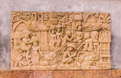 Sculpture on wall about Thai's way of life in garden. Sculpture on wall in garden. It is about way of life of Thai people in the past Stock Photography