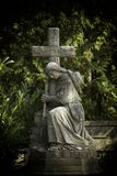 Grief. Sculpture of the woman with cross as symbol of the grief royalty free stock photos