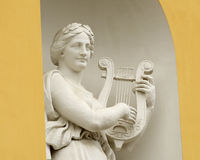 Sculpture of woman with lyre. Sculpture of woman with lyre on the facade of the theater Stock Photography