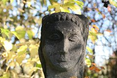 Sculpture of a woman. Portrait of a woman. Stone head. Autumn colors. Ancient people The beauty of the sculpture royalty free stock photo