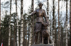 Sculpture of a woman sapper with a service dog shepherd Stock Images