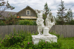 The sculpture of women farmers, bearing a jar of milk. White sculpture of women farmers, bearing a flask of milk among blooming wild rose Stock Image