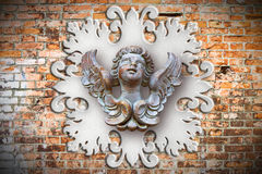 Sculpture of a wooden angel against an old classical plaster fra Stock Photo