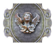 Sculpture of a wooden angel against an old classical plaster fra Royalty Free Stock Photo