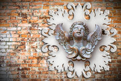 Sculpture of a wooden angel against an old classical plaster fra Stock Image