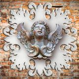Sculpture of a wooden angel against an old classical plaster fra Stock Images