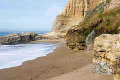 Sculptured Beach. Interesting rock formations and waterfall Royalty Free Stock Photo