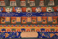 Sculptured masks of lion and painted floral patterns decorate the gate of a buddhist temple in Gangtey (Bhutan) Royalty Free Stock Photo