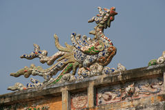 A sculptured phoenix decorates the ridgepole of a palace in Hue (Vietnam) Royalty Free Stock Photography