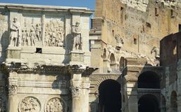Sculptures arch of Constantine and the Colosseum ruins. Bas-reliefs and sculptures on the triumphal arch of the Constantine emperor in Rome Royalty Free Stock Photos