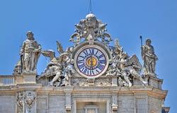 Sculptures and clock on the facade of Saint Peter basilica Stock Photos