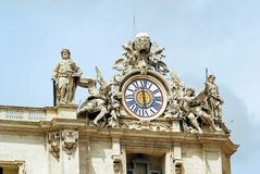 Sculptures and clock on the facade of Vatican city works Stock Photos