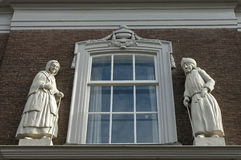 Sculptures of elderly man and woman, Zaltbommel. Frontage of former home for old men and women, housing for social care, charity, retirement home, convent. The Royalty Free Stock Image